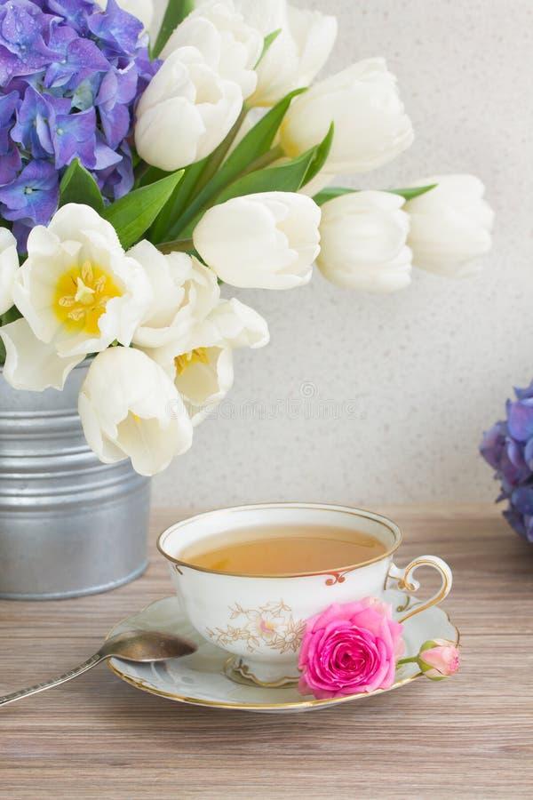 Antieke kop thee met tulpen royalty-vrije stock foto