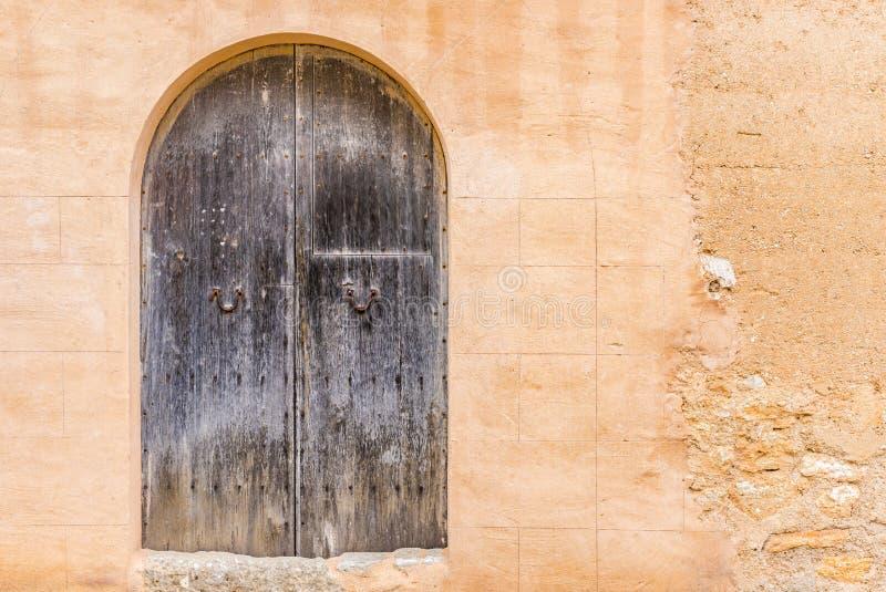 Antieke oude grijze houten voordeur met steenboog en rustieke steenmuur royalty-vrije stock afbeeldingen