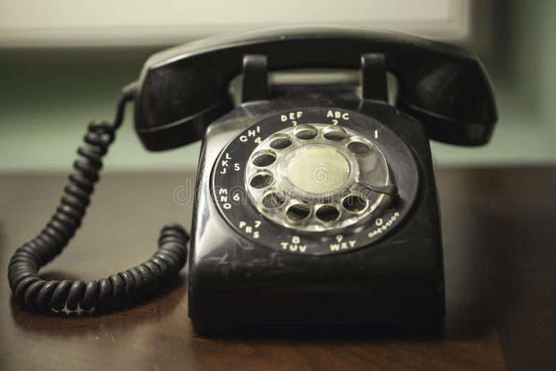 Antieke retro uitstekende zwarte roterende telefoon met gerold koord op een houten bureau royalty-vrije stock afbeelding