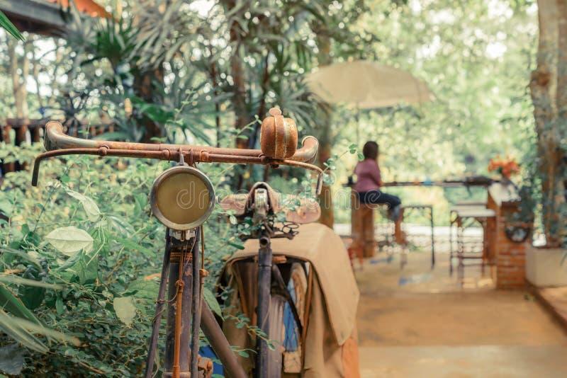 Antieke roestige die fiets voor decoratie in tuin wordt geparkeerd stock afbeeldingen