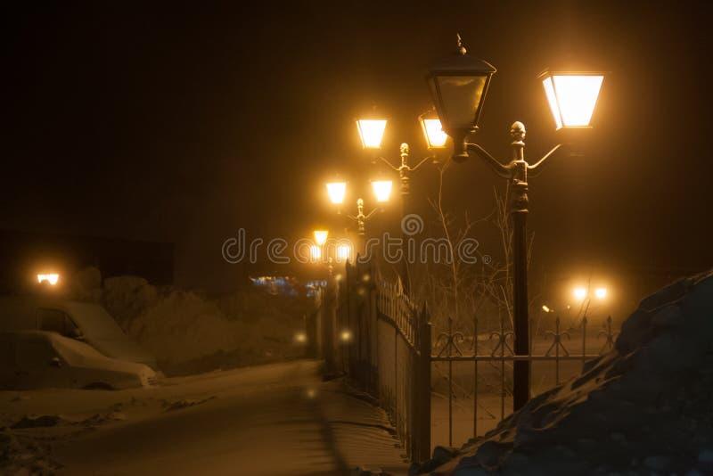 Antieke straatlantaarns op ijzer-vervaardigde omheining in de sneeuw Norilsk stock foto's