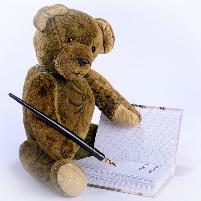 Antieke Teddy schrijft met een vulpen in een boek stock fotografie