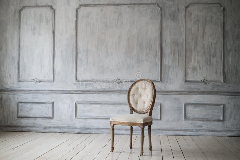 Antieke witte stoel over van de het ontwerp bas-hulp van de luxe lichte muur van de gipspleisterafgietsels roccocoelementen royalty-vrije stock foto