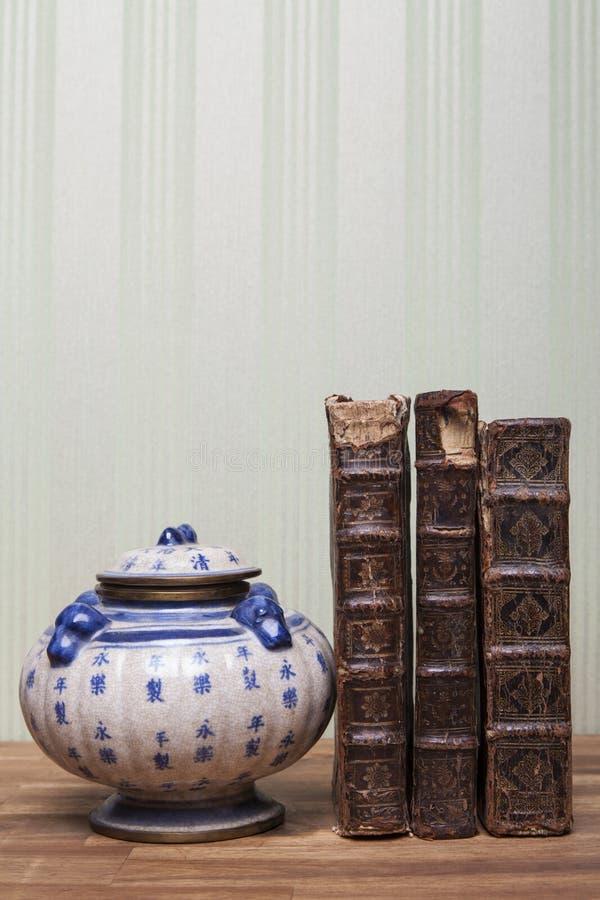 Antigüedades, tetera china, jarrón de té, tazón de azúcar, junto con libros antiguos foto de archivo libre de regalías