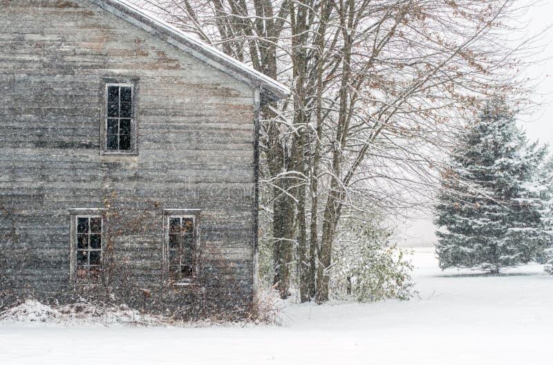 Antiga casa de fazenda em um dia de neve imagens de stock