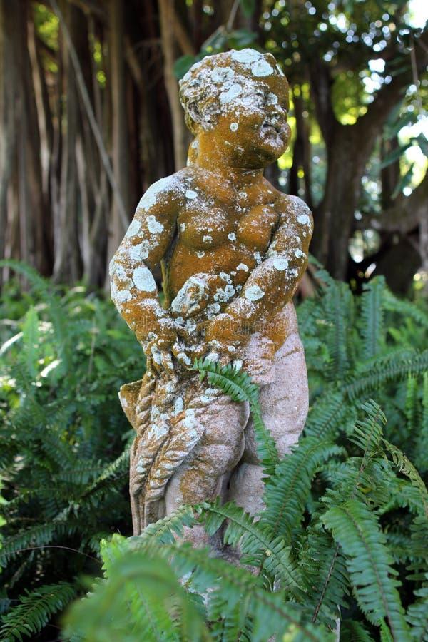 Antiga estátua de anjo bebê em um jardim foto de stock royalty free