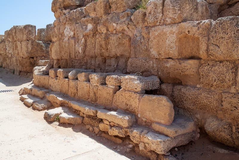 Antigamente sistema público de latrina/banheiro no parque arqueológico da cidade portuária de King Herod, Caesarea Maritima imagem de stock
