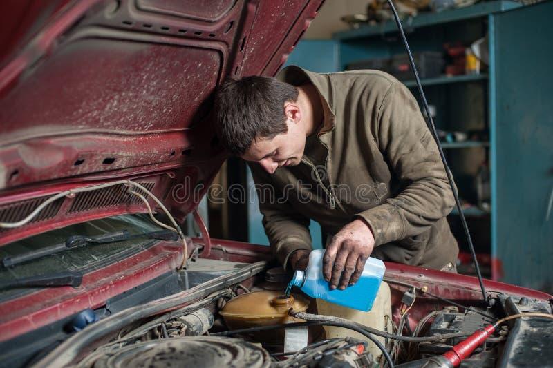 Antigel se renversant de travailleur d'homme de mécanicien dans le système de refroidissement photo stock