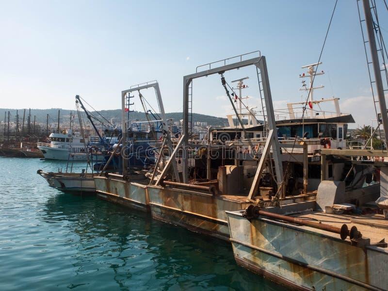 Antigos barcos-pescadores enferrujados com mecanismos de içamento de guincho no porto imagem de stock royalty free