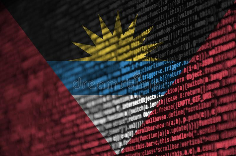 Antigua and Barbuda flag is depicted on the screen with the program code. The concept of modern technology and site development royalty free stock photo