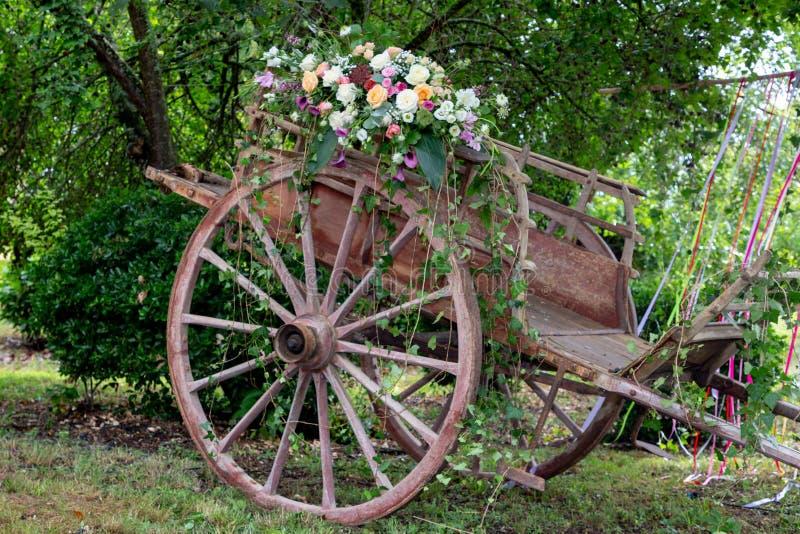 Antigua carreta de madera pintoresca decorada con flores para una boda foto de archivo