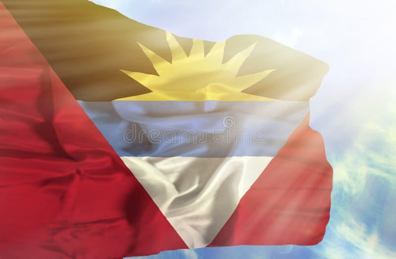 Antigua en de golvende vlag van Barbuda tegen blauwe hemel met zonnestralen royalty-vrije stock afbeelding