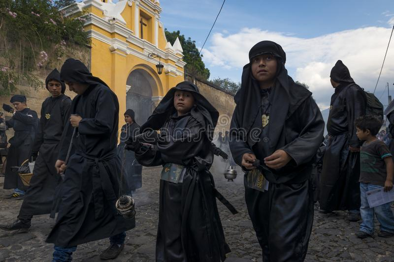 Young boys wearing black robes and hoods spreading incense in a street of the city of Antigua during a procession of the Holy Week royalty free stock photos