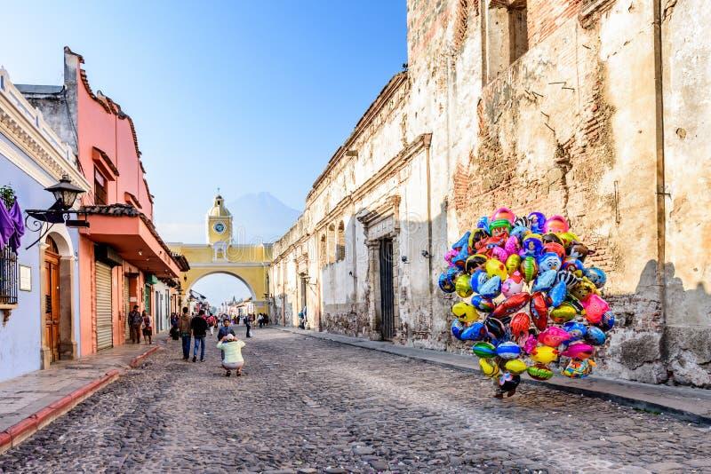 Balloon seller in street with Santa Catalina arch, ruins & volcano, Antigua, Guatemala stock photo