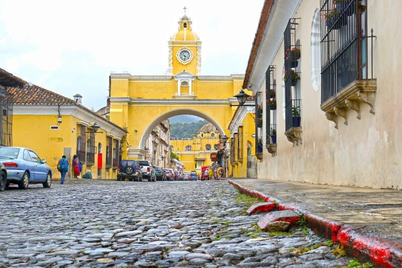 Antiguastad, Guatemala Den gula bågen på den huvudsakliga gatan Koloniala byggnader och kullersten stenar gatan arkivfoto