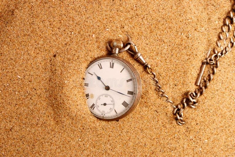 Antigue Taschenuhr im Sand stockbilder