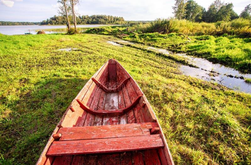 Antiguo barco pesquero de madera roja en el lago en verano imagen de archivo libre de regalías