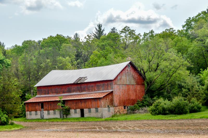Antiguo granero rojo enclavado en un bosque en Wisconsin fotos de archivo