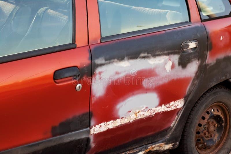 Antiguo umbral oxidado y puerta de un auto rojo imágenes de archivo libres de regalías