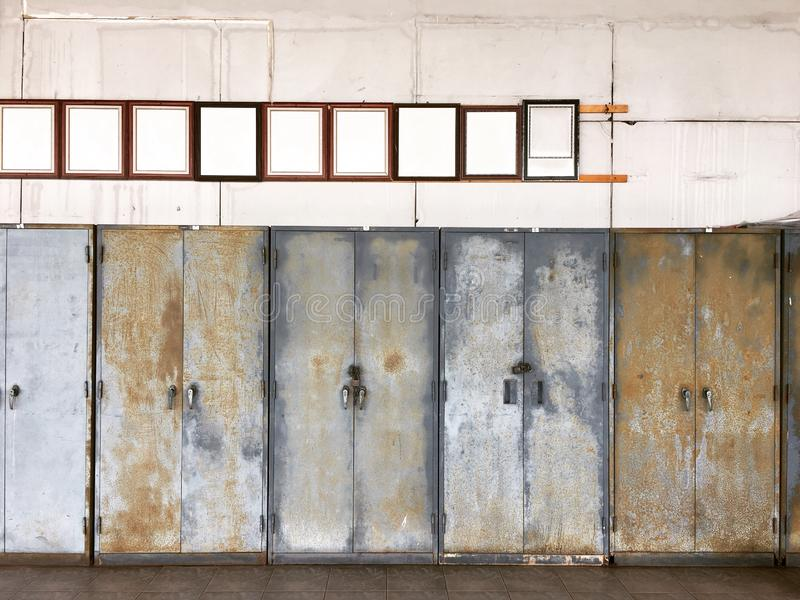 Antik brun träfotoram på den smutsiga väggen över gamla stålkabinetter arkivfoto