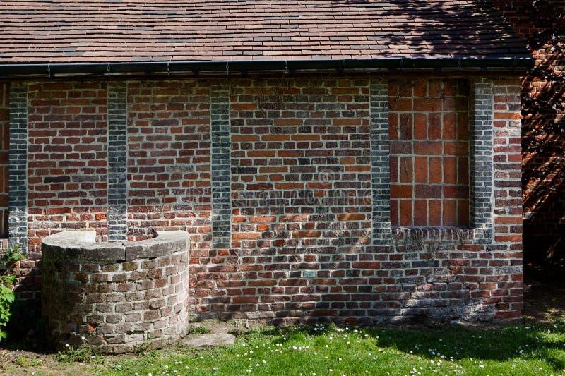 Antik brunn för ljus för väggtegelstensol, Groot Begijnhof, Leuven, Belgien royaltyfria bilder