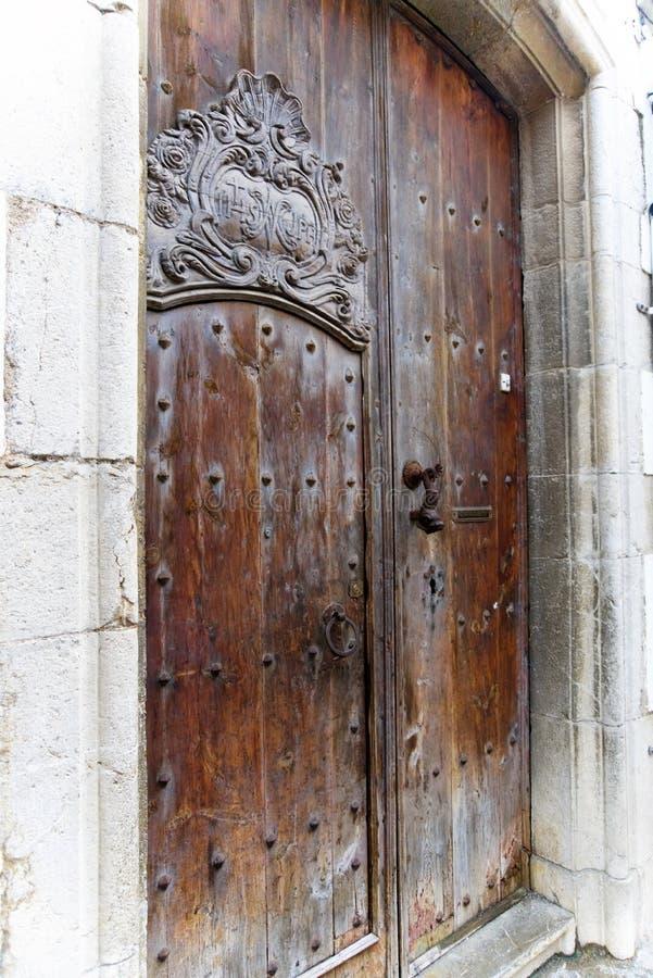 Antik dörr av ett spanskt hus med ett ärrhandtag och metallnitar arkivfoto
