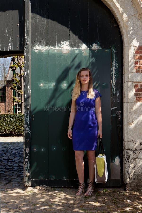 Antik dörr för blond kvinna, Groot Begijnhof, Leuven, Belgien fotografering för bildbyråer