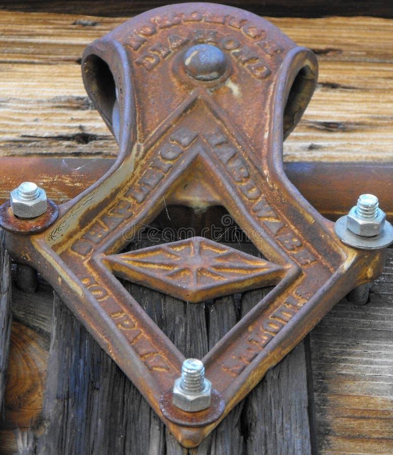 Antik dörrglidbana på en ladugårddörr royaltyfria foton