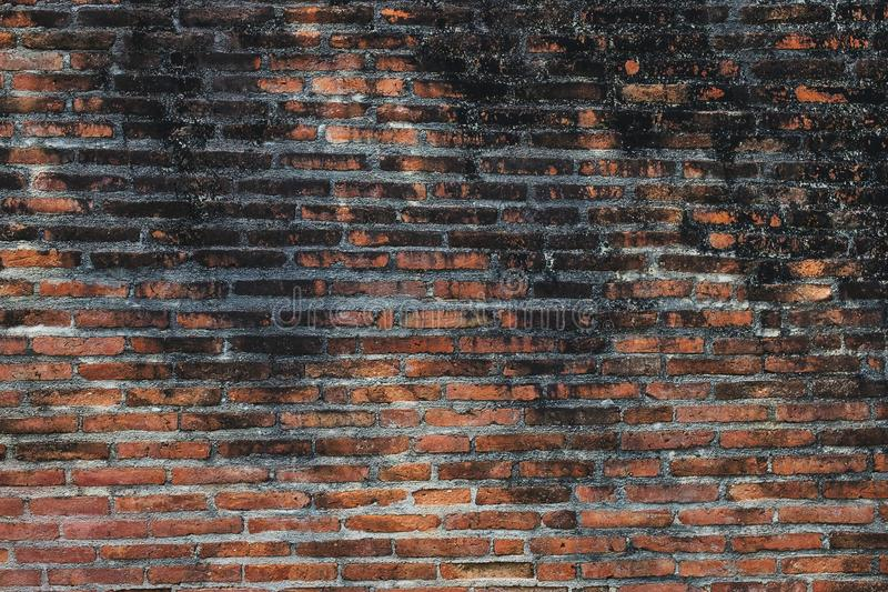 Antik forntida gammal smutsig vägg för röd tegelsten på den stads- gatan arkivbilder