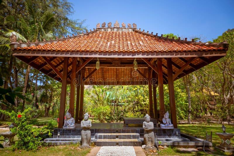 Antik gazebopaviljong med en asiatisk stilpagod för tak I en tropisk trädgård för sommar En stenbana som statyerna står längs arkivfoton