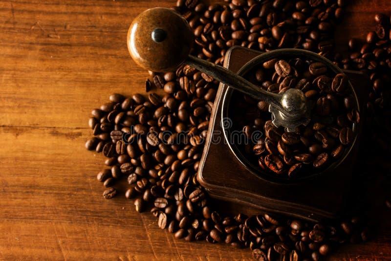 Antik kaffekvarn med kaffebönor arkivfoto