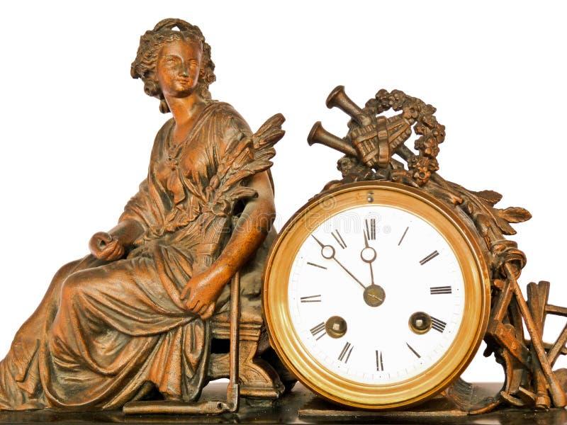 Antik klocka med mässingskvinnasammanträde- och musikinstrument arkivfoto
