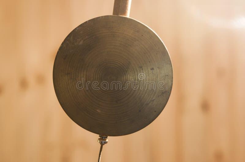 antik klockaklockpendel över träbakgrund arkivfoton