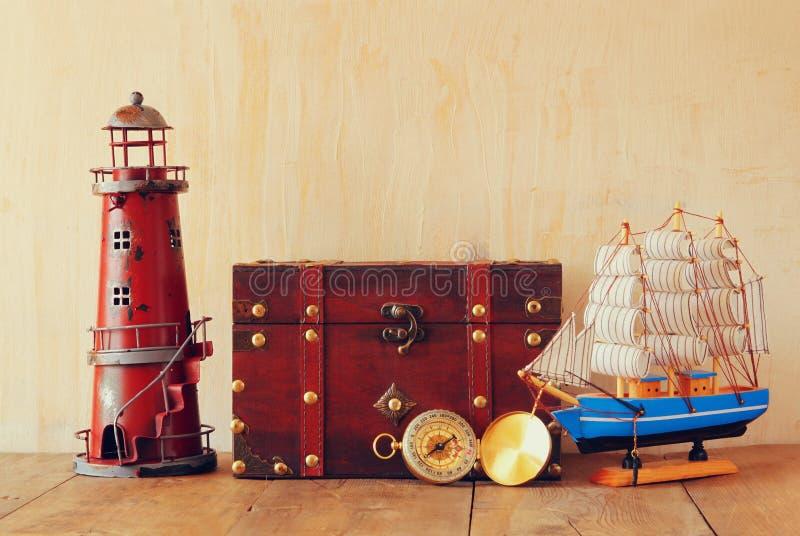 Antik kompass, tappningfyr, träfartyg och gammal bröstkorg på trätabellen royaltyfri foto