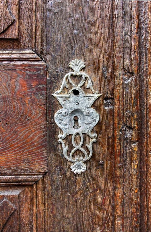 Antik nyckelhål på gammal paneled trädörr arkivbild