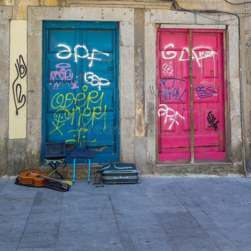 Antik portugisisk arkitektur: Gamla färgrika dörrar, handstilar och gitarr i gatan - Portugal arkivbild