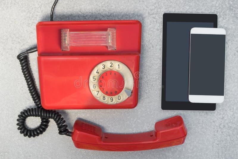 Antik roterande telefon med moderna trådlösa apparater arkivbild