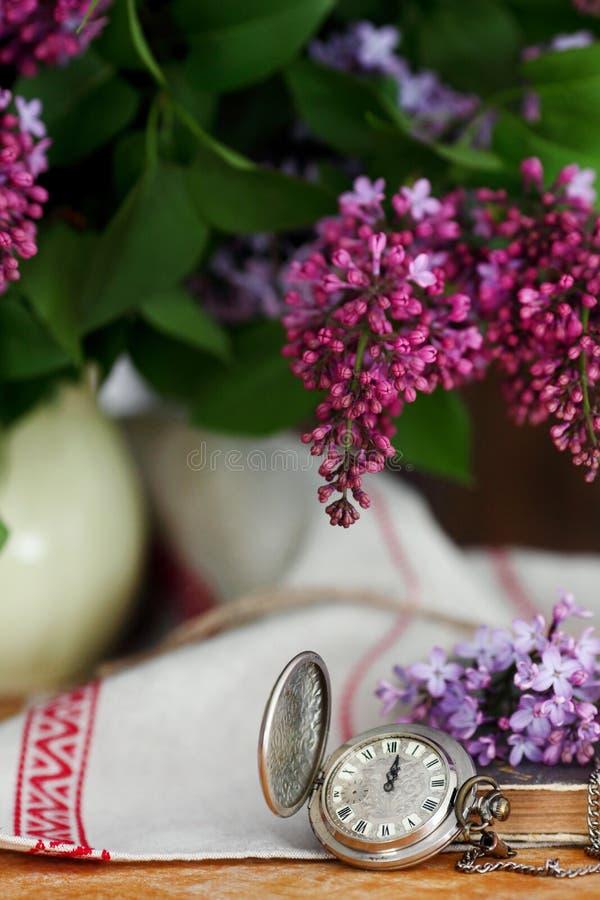 Antik rova på en träbakgrund, med lila blommor royaltyfri bild