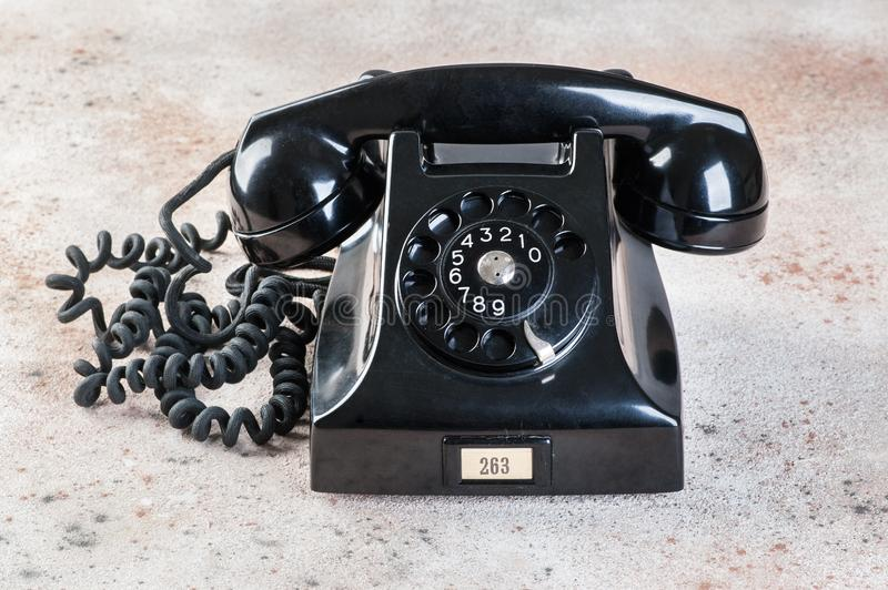 Antik svart roterande telefon på konkret bakgrund arkivfoton