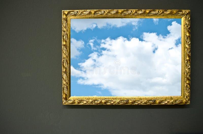 Antik tom guld- ram på grungeväggen med himmelfotografiet royaltyfria bilder