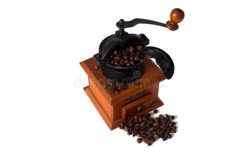 Antik träkaffekvarn med kaffebönor royaltyfria bilder