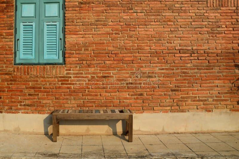 Antik trästol mot en grungy tegelstenvägg med det träblåa fönstret, tappningbakgrund royaltyfria foton