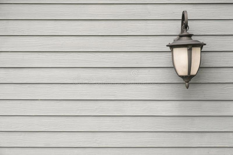 Antik vägglampa för tappning på den gråa wood väggen, för bakgrund med arkivfoto
