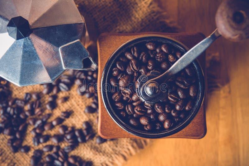 Antika kaffekvarnar med kaffebönor och mokaen lägger in royaltyfria bilder
