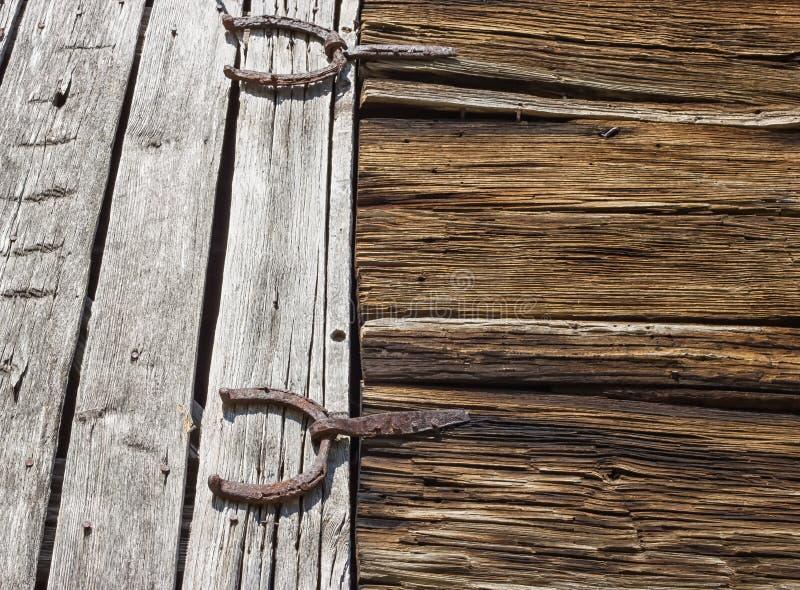 Antika ladugårddörrgångjärn som formas som hästskor fotografering för bildbyråer