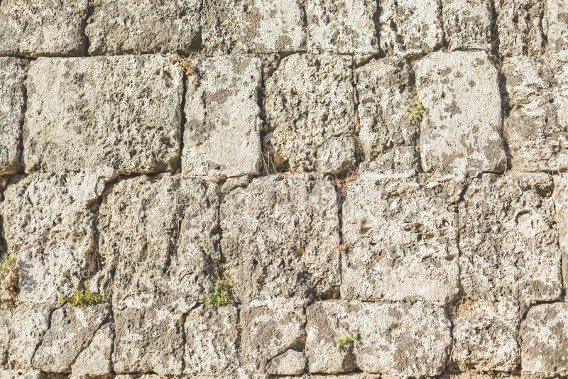 Antika naturliga stonewall Bakgrund av den forntida tegelstenväggen Textur av den gamla amfiteaterstenen för design Varvat vaggar arkivbild