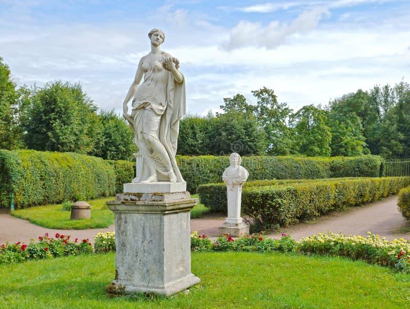 Antika statyer i blommaträdgården royaltyfri bild