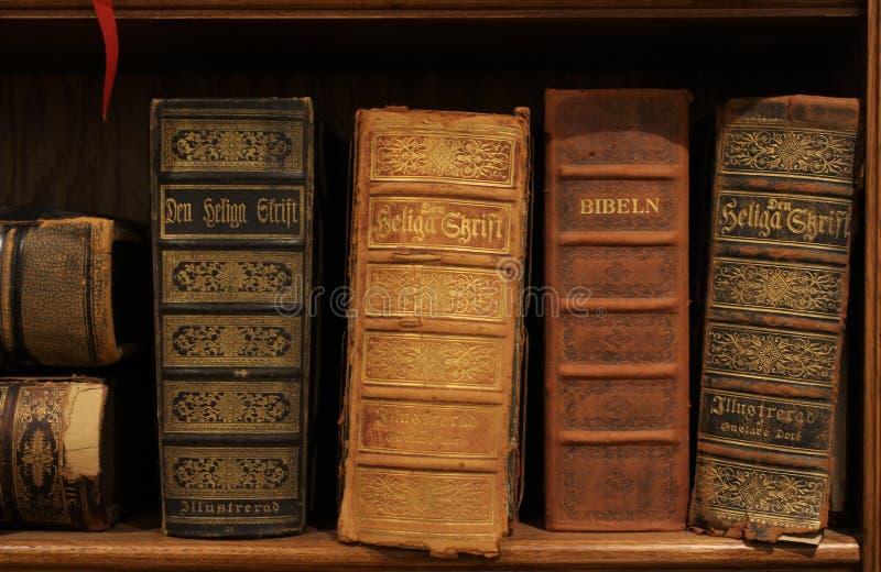 Antika svenska biblar på en hylla royaltyfria foton