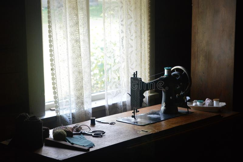 Antika symaskin- och sömnadaningar royaltyfria foton