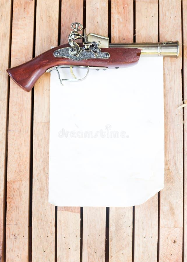 Antike Feuerwaffen mit leerem Papier auf dem Bretterboden lizenzfreie stockfotos